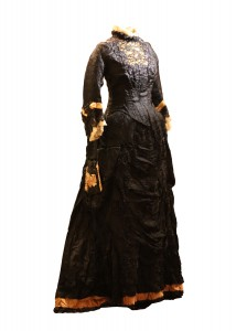 Black silk and lace dress with gold ribbon trim circa 1870